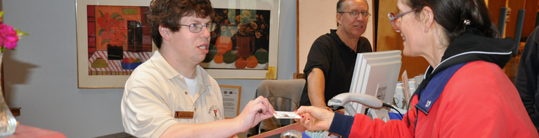 Young man working behind the counter at the YMCA, handing a membership card to a smiling  gym member